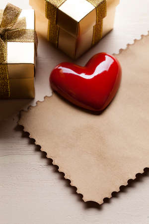 Red heart and two gold gift boxes and paper card