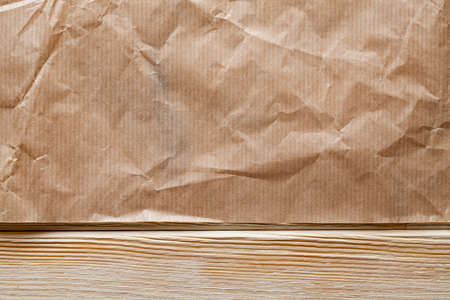 Crumpled paper sheet on wooden table Stock Photo