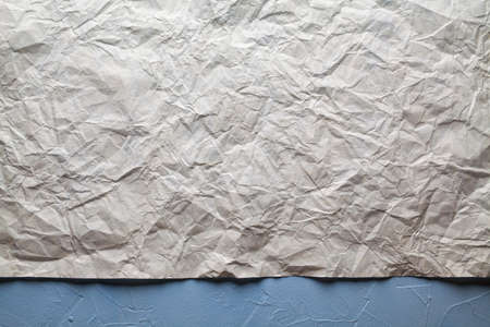 Crumpled paper sheet on plastered wall background