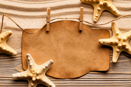 sheet of paper: Starfishes and blank paper sheet on beach sand Stock Photo