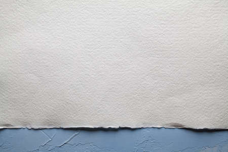 White paper sheet on plastered wall background
