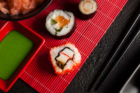 Sushi rolls, ginger and wasabi on red mat and black table Banco de Imagens