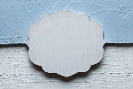 Blank wooden label on plastered wall background