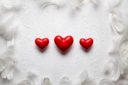 Three small red hearts and feathers on white plastered background