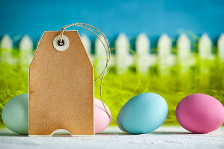 Colored Easter eggs and blank paper label on green and blue backgrond