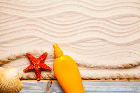 Suntan oil and starfish on beach sand background Imagens