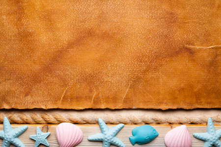 Blank handmade paper sheet and seashells on wooden and sand background