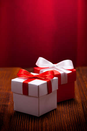 White and red gift boxes on wooden table and red curtain background Stock Photo