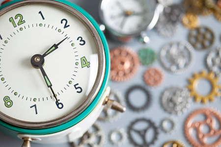 Antiguo reloj despertador vintage retro y engranajes de reloj en mesa gris Foto de archivo