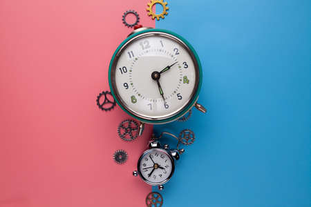 Two old alarm clocks and small gears, parts of the watch on a two-colored background Stock Photo - 125242787