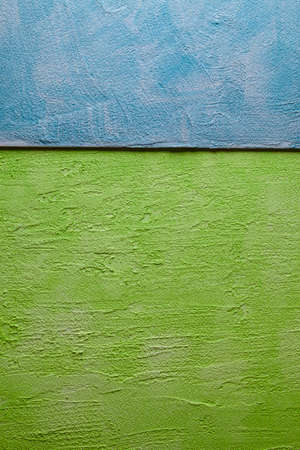Two colored green and blue uneven surface of the plastered wall