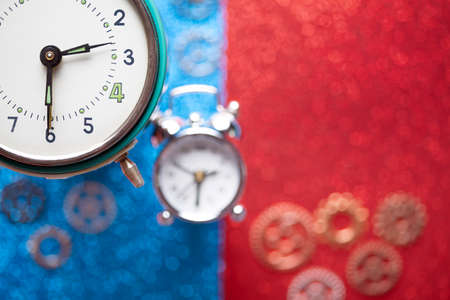Alarm clock and small parts of watch on red and blue abstract background Stock Photo - 125242842