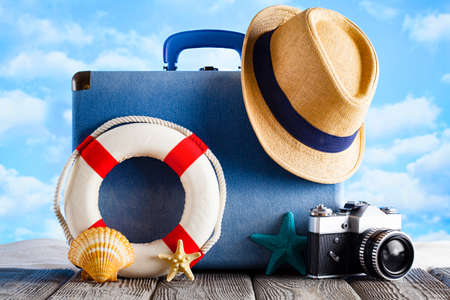 Holiday travel concept - suitcase, summer hat, photo camera, lifebuoy and shells on beach and wooden table background