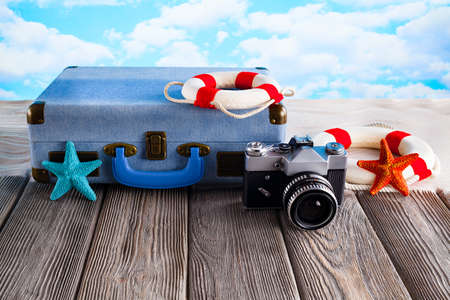 Summer holiday bag concept - suitcase, photo camera and lifebuoy on wooden table and beach Foto de archivo
