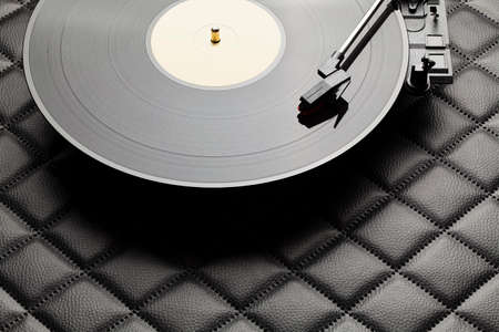 Vinyl record player and classic black vinyl record on leather background