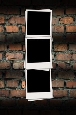 Three Blank Photos on Brick Background photo