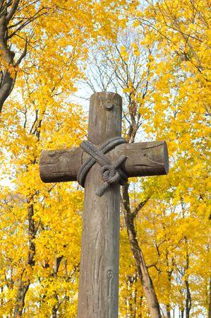 memorial cross: Antigua Cruz en el cementerio cat�lico sobre fondo amarillo de �rboles