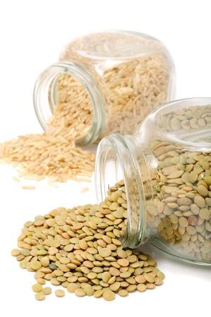 lentils: Frascos de vidrio con lentejas y arroz sobre fondo blanco
