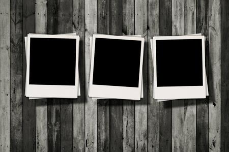 trois: Trois Polaroids blancs sur fond de bois sombre Banque d'images