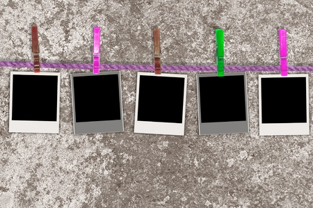 Five Blank Photos on Rope Against Grungy Background photo