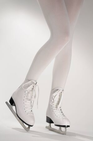 Woman�s Legs in White Ice Skates photo