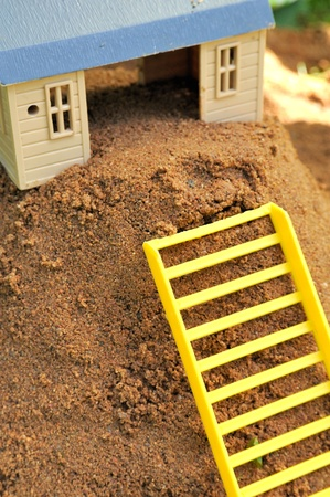 property ladder: Toy House with Ladder on Sand Stock Photo