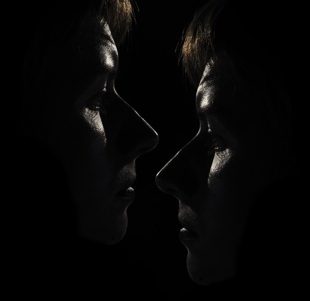 Two Womens Faces in the Dark