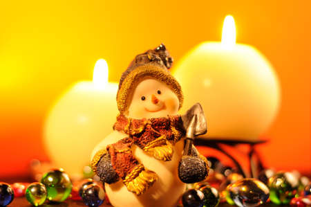 Christmas Evening � Snowman Figurine and Burning Candles on Yellow Background photo