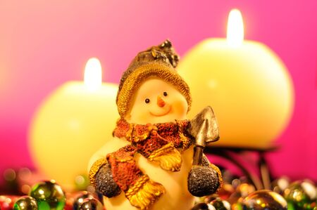 Snowman Figurine and Burning Candles on Romantic Pink Background photo