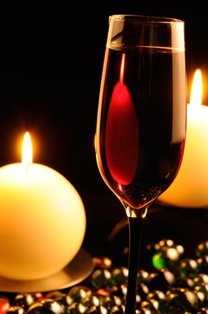Romantic Dinner - Glass of Red Wine and Burning Candles photo