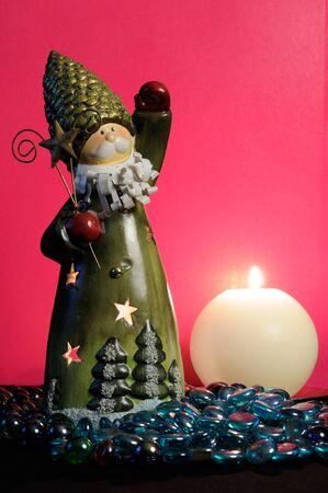 candleholder: Santa Claus Candleholder and Burning Candle on Romantic Pink Background Stock Photo