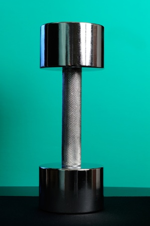 Heavy Metal Dumbbell on Turquoise Background photo