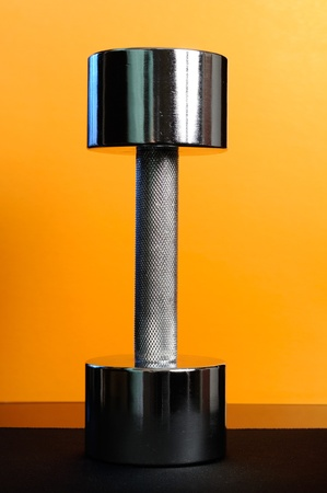 Metal 10-Pound Dumbbell on Orange Background photo