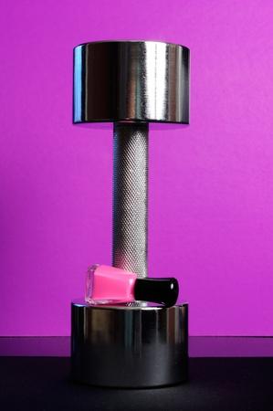 Shiny Dumbbell with Pink Nail Polish on Purple Background photo