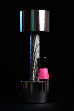 Metal Dumbbell with Pink Nail Polish on Black Background photo