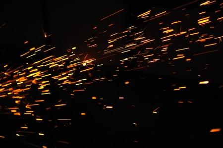 暗闇の中で火花の熱烈な流れ