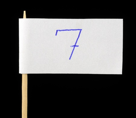 Handwritten Number Seven on Paper Flag on Black Background photo