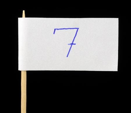 Handwritten Number Seven on Paper Flag on Black Background photo