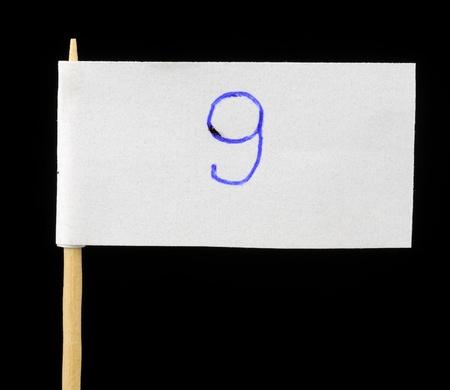 Handwritten Number Nine on Paper Flag on Black Background photo