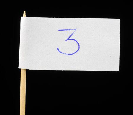 Handwritten Number Three on Paper Flag on Black Background photo