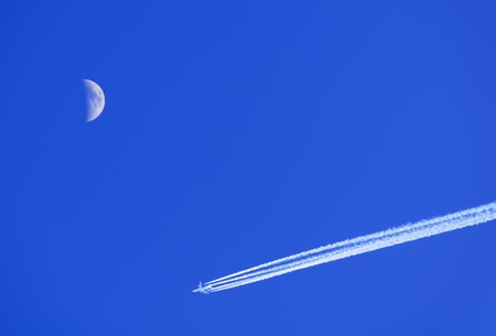 Blue Sky, Moon and Jet Aircraft with Condensation (Vapor) Trail photo