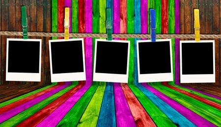 group picture: Fotos en blanco colgando de la cuerda en el fondo de madera multicolor