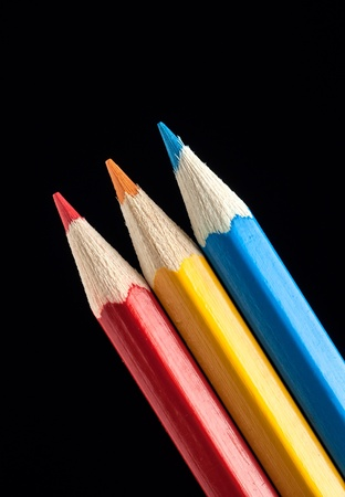 Blue, Yellow and Red Pencils on Black Background photo