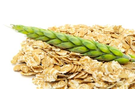 Wheat Flakes y espiga de trigo en el fondo blanco Foto de archivo