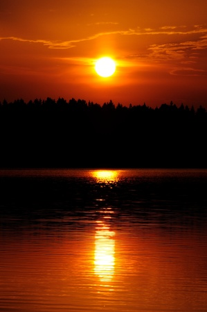 dawning: Setting Sun with Ray Path of Light on Water Stock Photo
