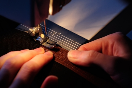 The hands of a seamstress sewing on a  hook-and-loop fastener 写真素材