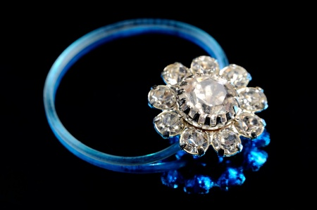 A beautiful toe ring with crystals in blue light on a black background photo