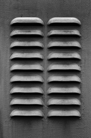 louvered: A dark gray metal ventilation louver with horizontal slats