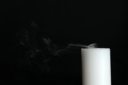 Smoke coming from a white candle isolated on black with copy space photo