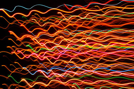 radiant light: Wavy multicolored glowing lines against a dark background (long exposure shot) Stock Photo